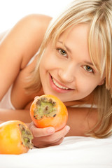 Portrait of young smiling woman with persimmons