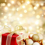 Christmas gift and baubles on defocused lights background poster
