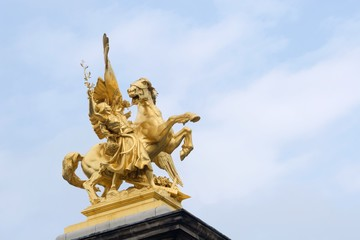 gold statue from alexandre III bridge in paris