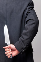 Businessman with a knife behind his back.