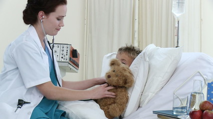 Female doctor examining a little patient