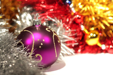 purple christmas ball with gold pattern on abstract tinsel backg