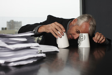 Mature businessman playing with cups