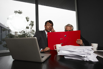Two businessmen hiding behind a folder