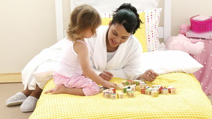 Mother playing with her daughter toy cubes on the bed