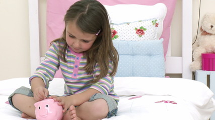 Little girl playing with a piggy bank on bed