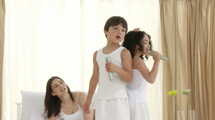 Family singing and dancing karaoke on bed with microphones