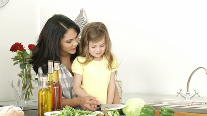 Mother and little girl cutting vegetables