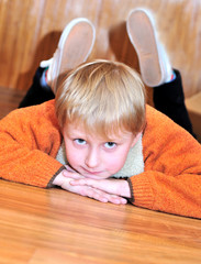 little boy laying on the wooden floor