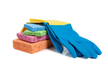 Multi-colored sponges and rubber gloves on a white background