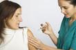 Junge Krankenschwester impft  eine Patientin