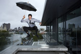 Businessman jumping in rain