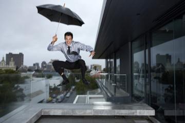 Businessman jumping in rain