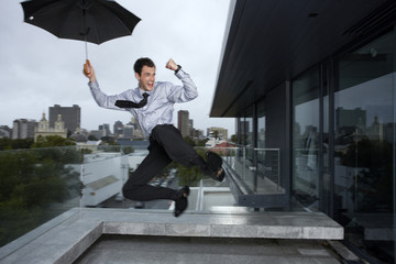 Businessman jumping in the rain