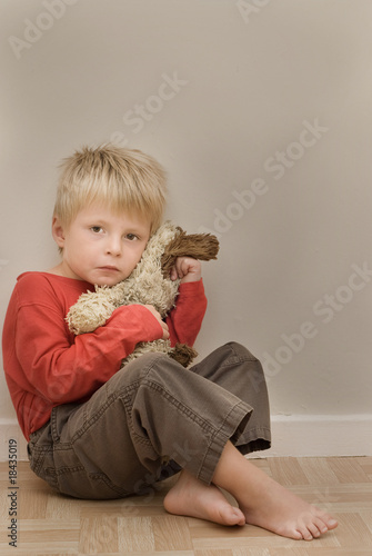Upset child cuddling his teddy.