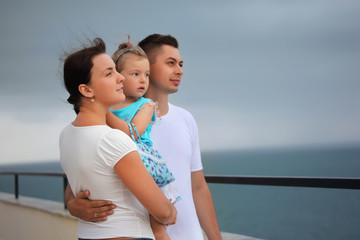 young man and beautiful woman protects little girl from wind