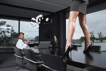 Businessman throwing trash at woman