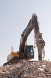 Excavator over a heap of rubbles poster