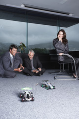 Businessmen playing with toy automobiles