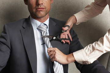 Woman cutting man's tie