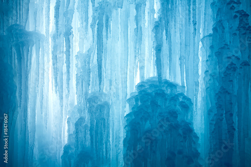 Leinwanddruck Bild A frozen waterfall with ice in a blue and white color in winter