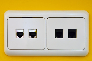 white computer network wall plug on yellow wall
