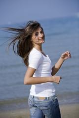 Beautiful woman running windblown on the beach
