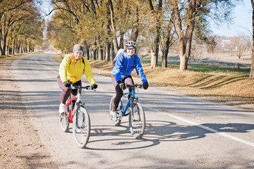 couple riding bicycles on road with autumn trees