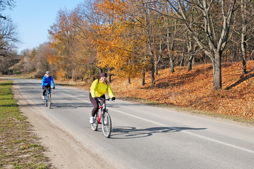 adults riding bicycles on road with autumn trees on sunny day