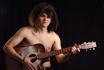 nude naked man with acoustic guitar at black