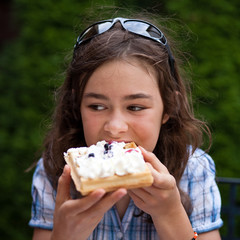 Girl eating cake with cream and fruits