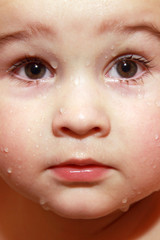 Close-up face baby with drops in bathroom