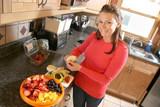 Woman Prepares Fruit Salad in Kitchen poster
