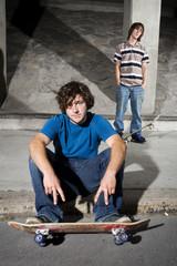 Two skateboarders in underground parking lot
