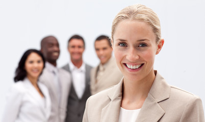 Portrait of smiling businesswoman in front of her team