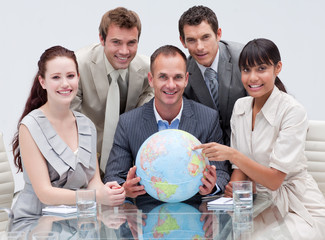 Smiling business team holding a terrestrial globe