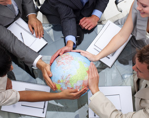 High angle of business team holding a terrestrial globe