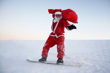 Weihnachtsmann balanciert mit Snowboard