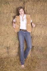 Woman by hay stack serious