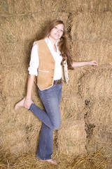 Woman by hay stack leg up