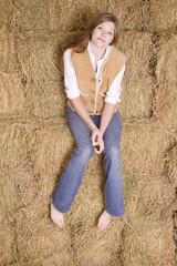 Woman sitting on hay serious