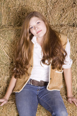 Woman  sitting on hay stack smiling