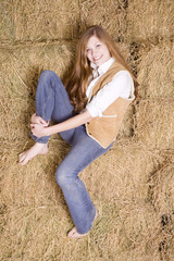 Woman sitting on haystack leg