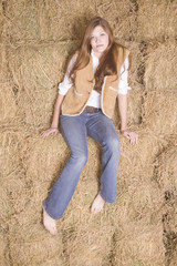 Woman sitting on haystack serious