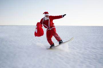 Junger Weihnachtsmann beim Snowboarding