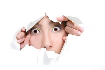 young girl peeping through hole in white paper