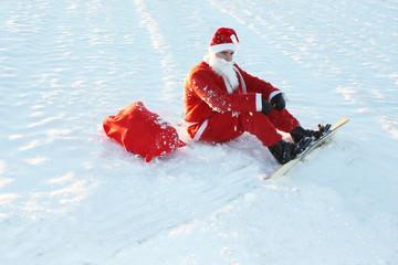 Weihnachtsmann mit Snowboard sitzt im Schnee