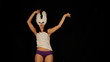 beautiful young masked woman dances to the groove