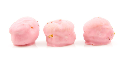 Three pink  cream puffs in a row over white background