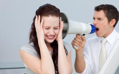 Businessman shouting through a megaphone at his colleague